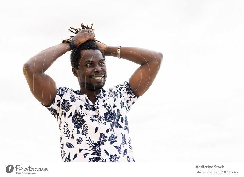 lächelnder schwarzer Mann, der sein Haar in einem Schwanz hält Afrikanisch Behaarung männlich jung Amerikaner Afro-Look berührend Typ Glück gutaussehend Blick