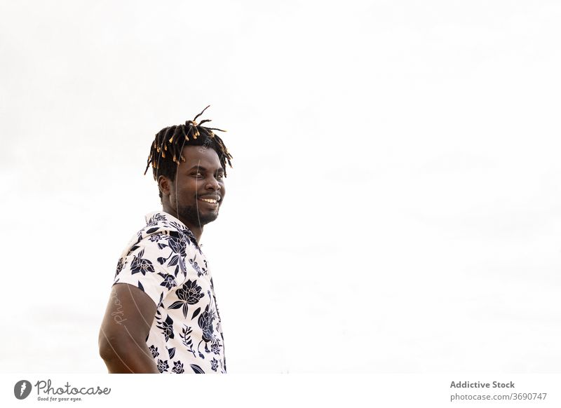 stilvollen jungen schwarzen Mann mit Blume Shirt lächelnd Person männlich Lächeln Glück Textfreiraum Afrikanisch Porträt vereinzelt Typ gutaussehend Blick