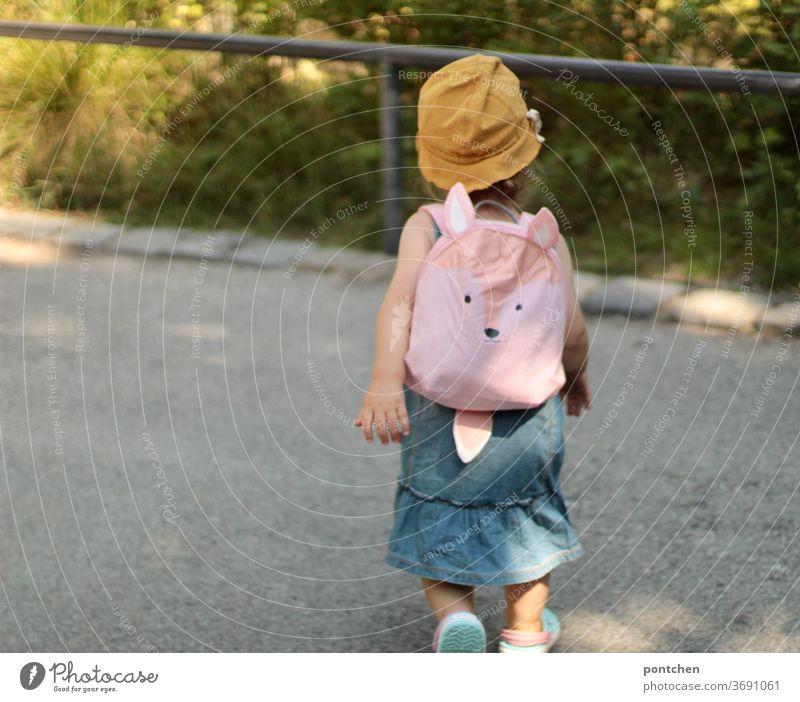 Ein Kleinkind mit einem gelben Sonnenhut und einem süßen Rucksack in rosa. Familienausflug, Familienurlaub rucksack urlsub reise kleidung sommer selbstbewusst