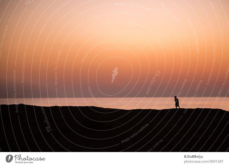In der Morgendämmerung ist eine Silhouette auf dem Strand unterwegs, warum nur, was treibt sie an.... dahinter öffnet sich der Blick auf den Golf des Omans.