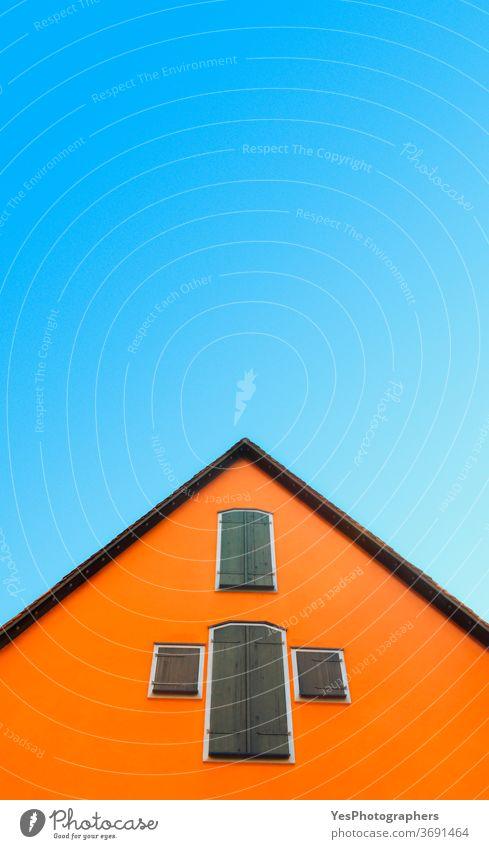 Orangefarbenes Haus gegen blauen Himmel. Haus mit orangefarbenen Wänden minimalistisch. Deutsche Architektur Deutschland abstrakt Antiquität Dachboden