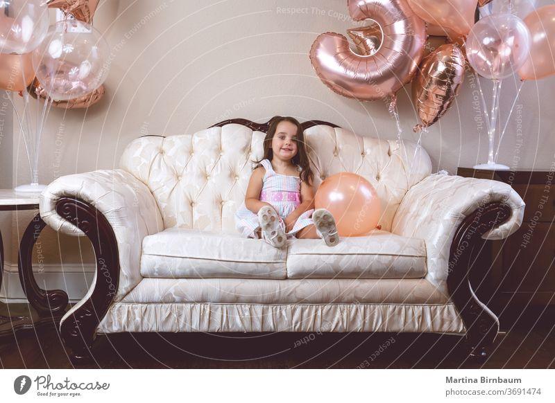 3-jähriges Geburtstagskind spielt mit ihren Luftballons auf der Couch Kind Kleinkind Mädchen 3-8 Jahre Feier Lächeln eine Person Liege im Innenbereich Kindheit