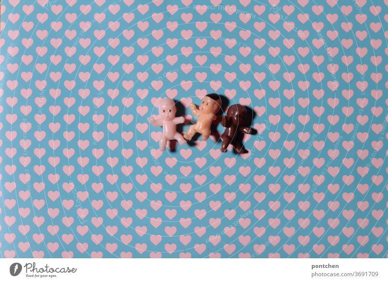 Drei kleine babypuppen mit verschiedenen Hautfarben liegen auf einem Untergrund mit Herzen. Liebe, Toleranz, Menschheit, vielfaltc Babies hautfarbe poc
