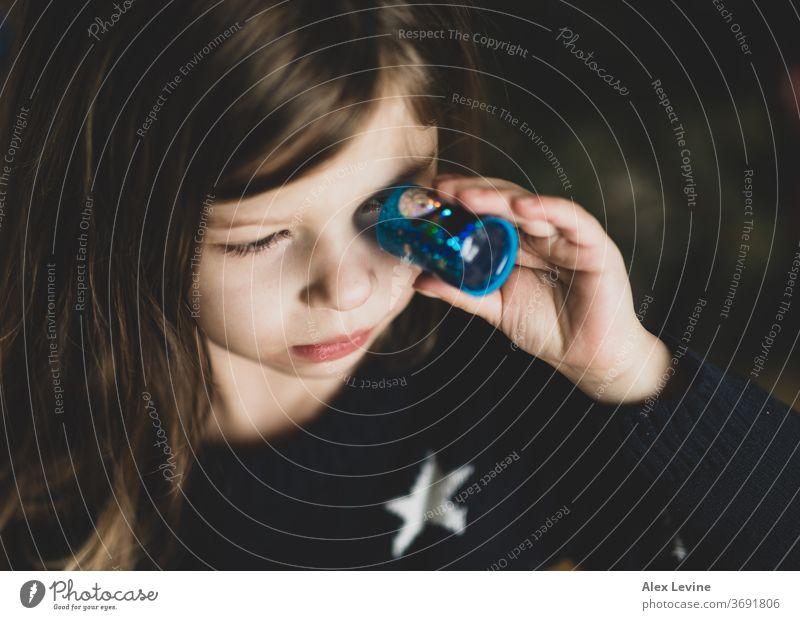 Kind schaut durch ein Spielzeug-Kaleidoskop Mädchen Blick Spielen jung spielerisch Wissenschaft Lernen