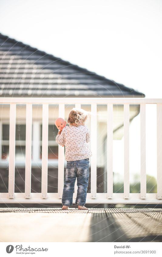Mädchen mit Puppe steht alleine auf dem Balkon und schaut von oben nach unten gucken draußen Gitter Zaun eingesperrt spielen beobachten einsam draußensein