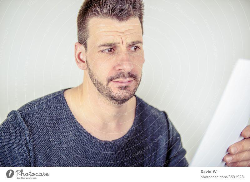 skeptischer Blick auf einen Zettel Mann Blatt lesen schauen Rechnung Denken Zweifel verwirrt überrascht Nachricht