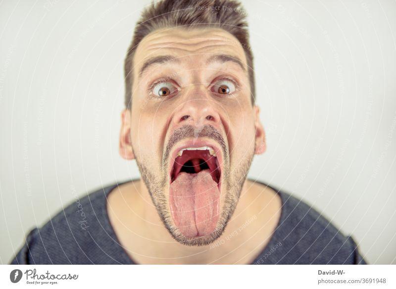 Mann schaut mit offenem Mund crazy in die Kamera weit geöffnet Zunge verrückt Profil Gesicht durchgeknallt Porträt Mund geöffnet lecken zunge zeigen