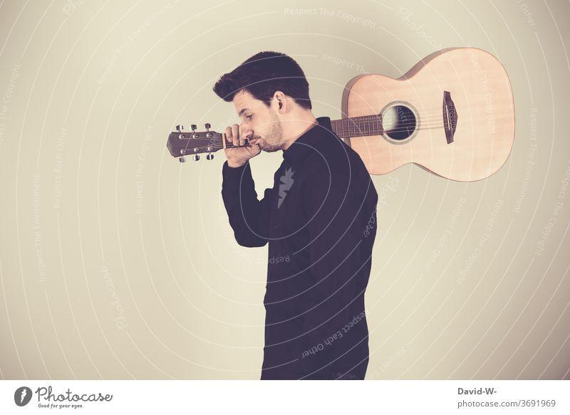 Corona - Musiker trägt seine Gitarre auf den Schultern und schaut betrübt nach unten Gitarrist pleite verbot musizieren auszeit Musikinstrument pandemie