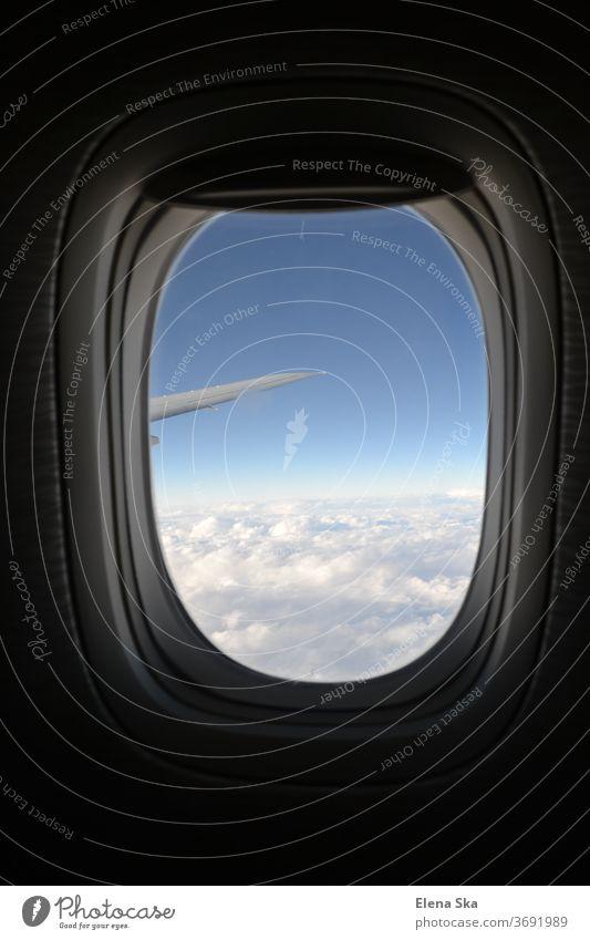 Rundes Fenster eines Flugzeugs mit der Ansicht auf Himmel, Wolken und Flügel Flugzeugfenster Fluggerät reisen Tourismus armosphäre