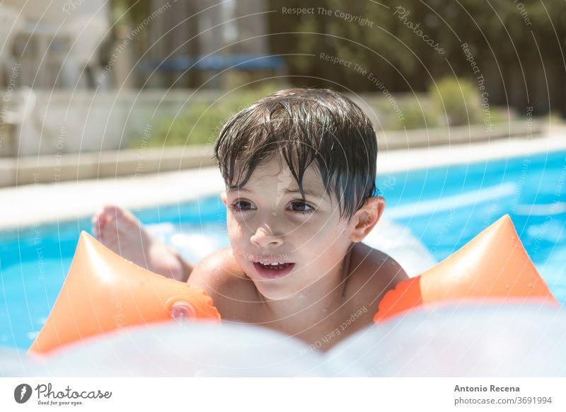 Kleinkind mit Muffen und schwimmt auf einer Matte in einem Schwimmbad oberirdisches Schwimmbecken vor Hinterhof Junge Windstille Kaukasier Kind Kindheit