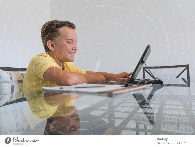Junge spricht mit einem Klassenkameraden während einer Videokonferenz auf einem Tablet und diskutiert Hausaufgaben, während er in einem modernen, hellen Raum am Tisch sitzt.