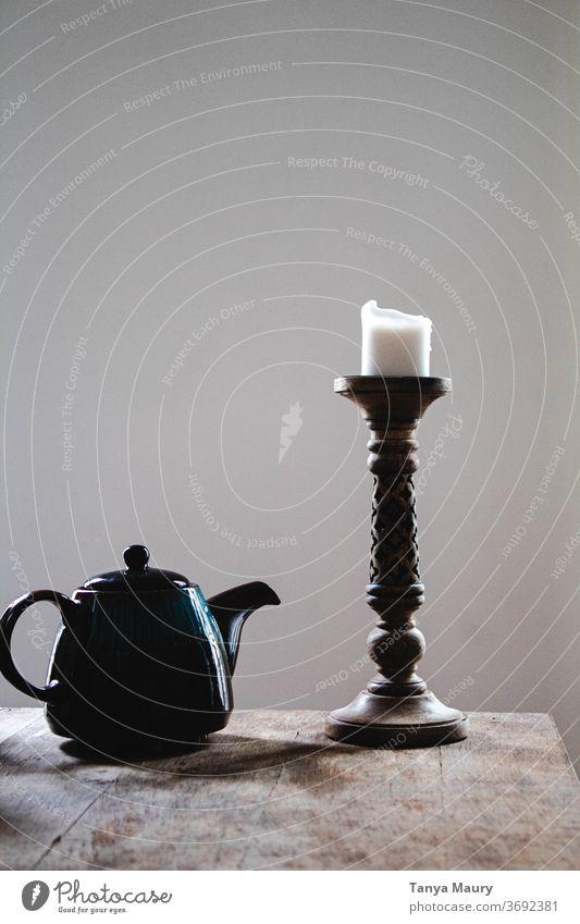 Blaue Teekanne und weiße Kerze auf einem Holztisch mit gräulichem Hintergrund Leuchter Innenaufnahme Beleuchtung Licht Dekoration & Verzierung grau