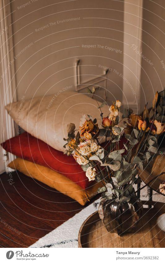 Gemütliches Wohnzimmer mit bunten Kissen und einer Vase voller Trockenblumen auf einem Holztisch Herbst Herbststimmung Atmosphäre November nordisch Hygge bequem