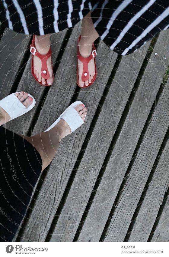 Füße am Steg von oben Schuhe Badeschuhe Sandalen Beine Holz Holzsteg Frau 2 Damenschuhe weiblich Außenaufnahme gesztreift Hose rot weiß grau Streifen Baden See