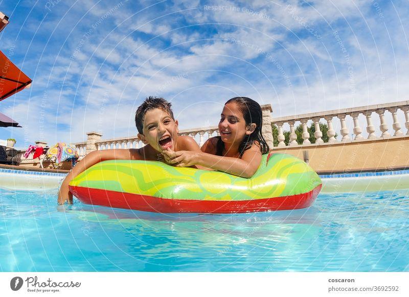 Zwei lustige Kinder im Pool auf einer Luftmatratze Aktivität blau sorgenfrei Kindheit niedlich genießen Familie Schwimmer Frische Freund Freunde Freundschaft