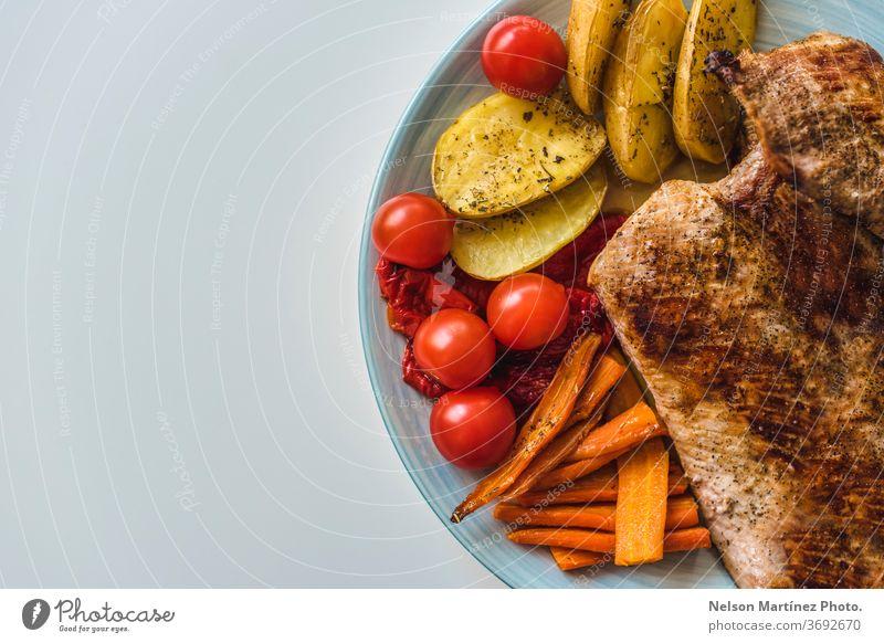 Gegrilltes Fleisch mit Gemüse. Tomaten, Karotten und Kartoffeln. Gesundes Essen. Ein flachgelegter Schuss gebratenes Fleisch, Kartoffeln, Karotten und Tomaten auf einem Teller