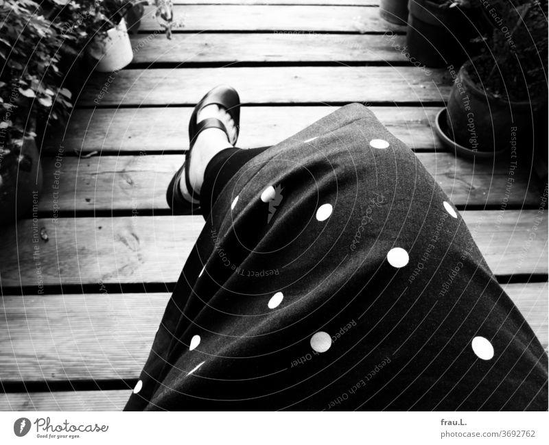 Auch sonntags sitzt die Frau auf ihrer Dachterrasse, dann am liebsten in ihrem schwarzen Kleid mit den weißen Punkten. Füße Blumentopf Holzbohlen Grätlinge