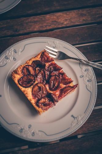 Ein Stück Pflaumen-dachi auf einem Teller bei der Oma Pflaumen-Dackel Pflaumenkuchen Kuchen lecker Tisch verschnörkelt altehrwürdig altmodisch Backwaren