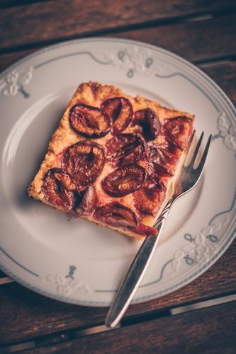 Ein Stück Zwetschendatschi auf einem Teller bei Oma Zwetschgendatschi Zwetschgenkuchen Kuchen Datschi lecker Tisch verschnörkelt vintage altmodisch Backwaren