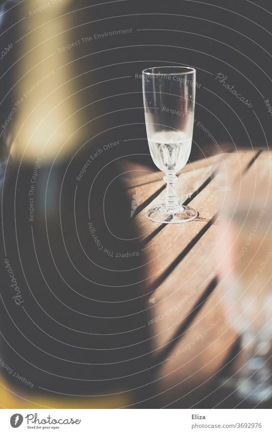 Ein Sektglas auf dem Tisch in der Sonne Prosecco Champagner Flasche Sommer trinken Alkohol fast leer Schluck Feste & Feiern Glas Schaumwein Getränk