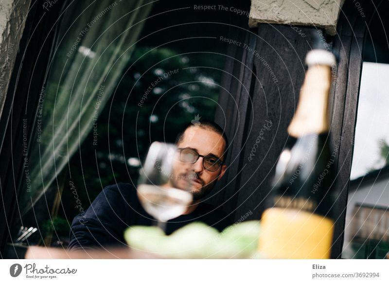 Das Gesicht eines Mannes hinter einem gefüllten Weinglas versteckt trinken grimmig Glas Alkohol Getränk Party Flasche Sektflasche Prosecco Restaurant draußen