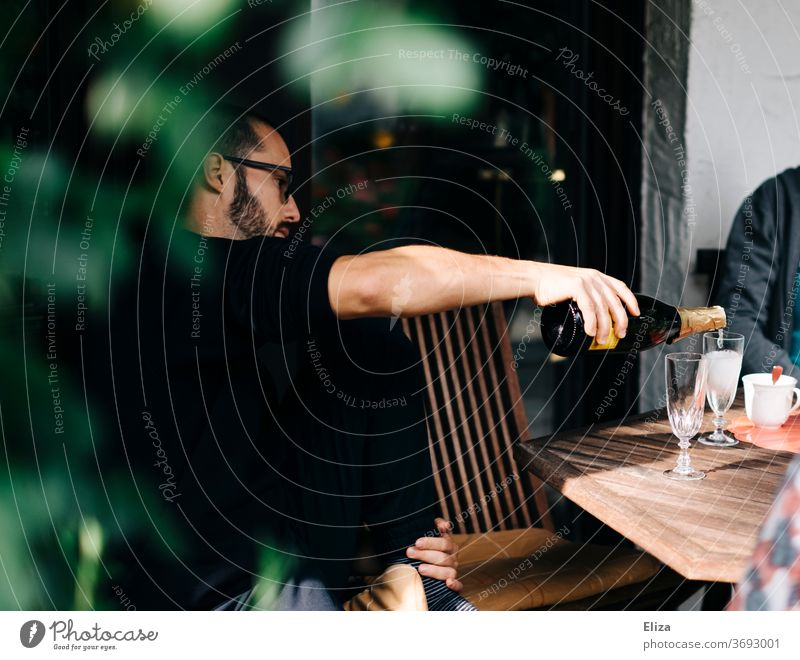 Ein Mann sitzt am Tisch im Garten und schenkt Prosecco in Gläser ein einschenken ausschenken Flasche Sekt Sektflasche Feier Daydrinking eingießen gemütlich