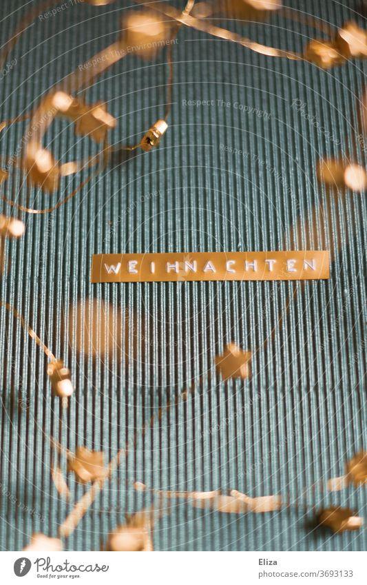 Schriftzug Weihnachten in gold auf blauem Hintergrund geschrieben golden Weihnachtskarte Text Dekoration Weihnachtsdekoration weihnachtlich