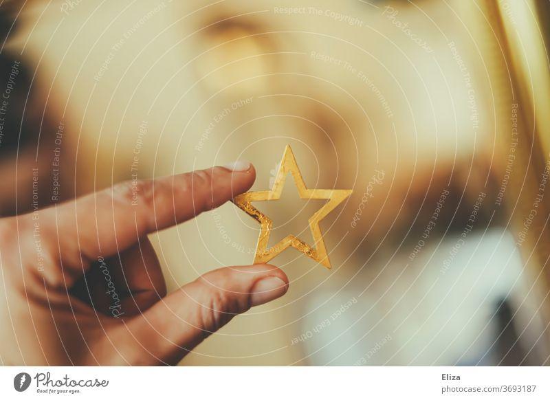 Hand hält einen goldenen Weihnachtsstern. Weihnachten. weihnachtlich Stern Weihnachtsdekoration Weihnachten & Advent Weihnachtsmotiv Stern (Symbol)