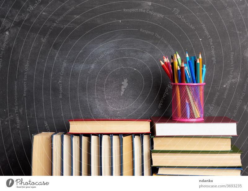 Stapel verschiedener Bücher, Briefpapier auf schwarzem Kreidehintergrund, zurück zur Schule Archiv Hintergrund Tafel blanko Holzplatte Buch braun Business