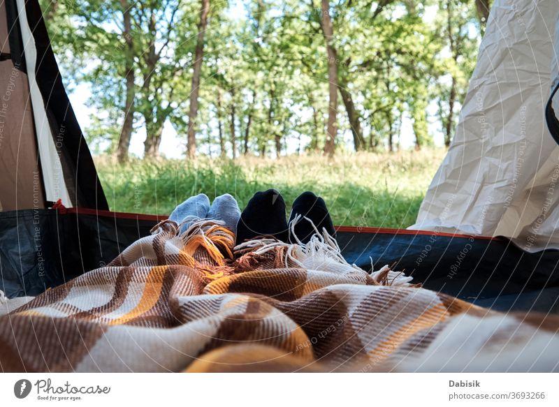 Zwei Personen liegen in einem Touristenzelt, Innenansicht. Füße unter den Decken im Zelt. Touristisches Lager im Inneren Wald Hintergrund Tourismus Natur wild