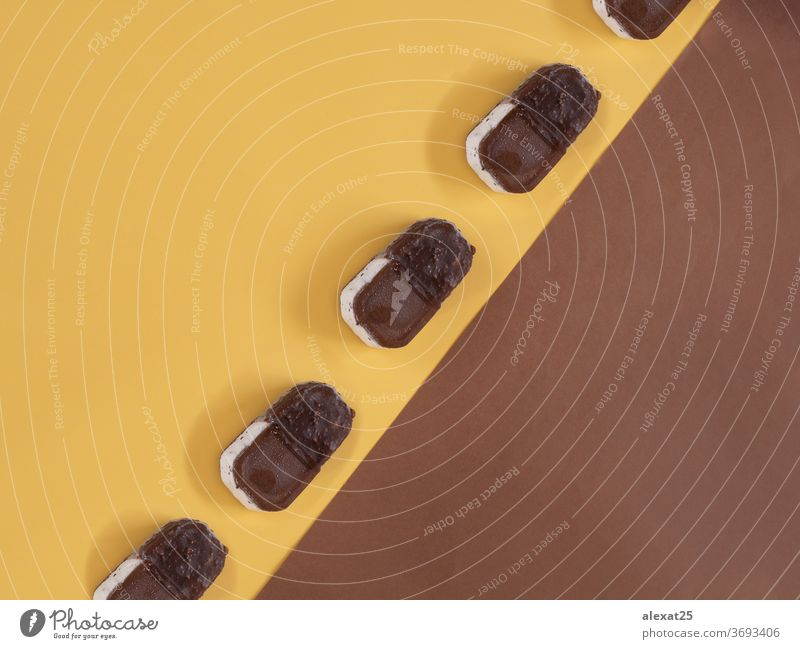 Eiscreme-Muster auf gelbem und braunem Hintergrund Biskuit Schokolade kalt farbenfroh Zapfen Sahne dekorativ lecker Dessert Gewebe Geschmack Lebensmittel