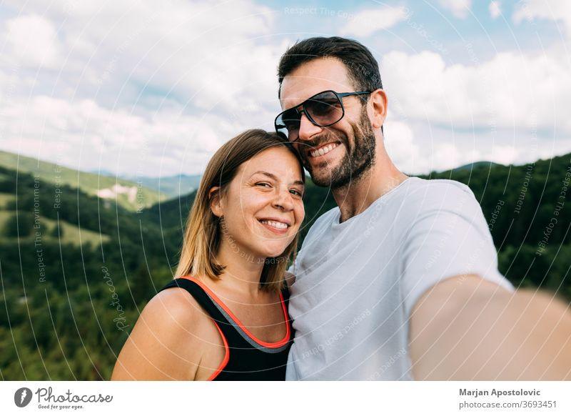 Junges Paar beim Egoismus in den Bergen Erwachsener Abenteuer schön Fotokamera Kaukasier Gesichter Frau Freiheit Freunde Glück Wanderung wandern Reise