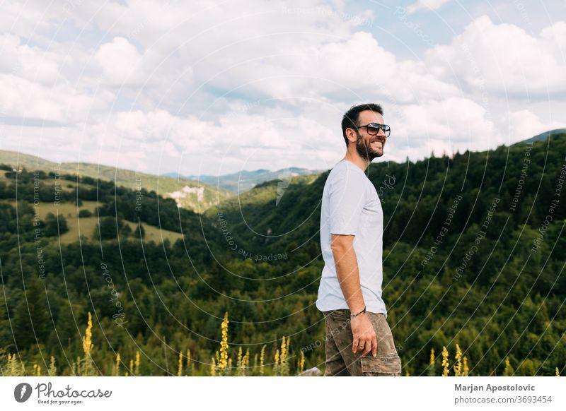 Junger männlicher Naturforscher auf dem Gipfel eines Gebirges Aktivität Abenteuer allein lässig Wolken Fundstück Ökologie Umwelt erkunden Entdecker Wald frei