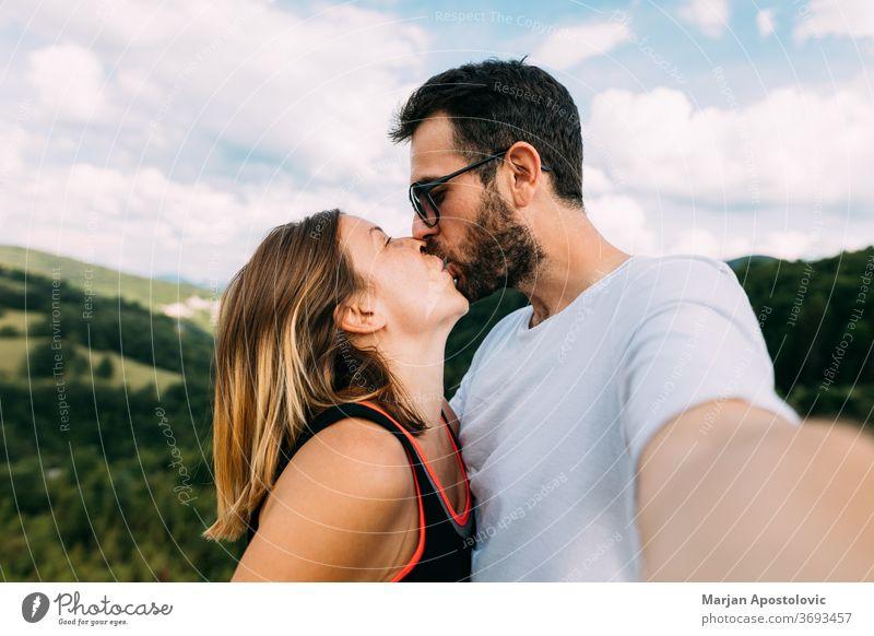 Junges Paar beim Küssen in den Bergen beim Selfie Erwachsener Abenteuer anhänglich schön Freund Fotokamera lässig Kaukasier heiter emotional erkunden Freundin
