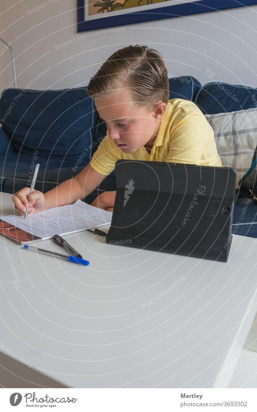 Kleiner Junge online mit seinen Klassenkameraden während einer Videokonferenzschaltung, macht seine Arbeit auf einem Notebook und teilt seine Mathearbeit mit ihnen.