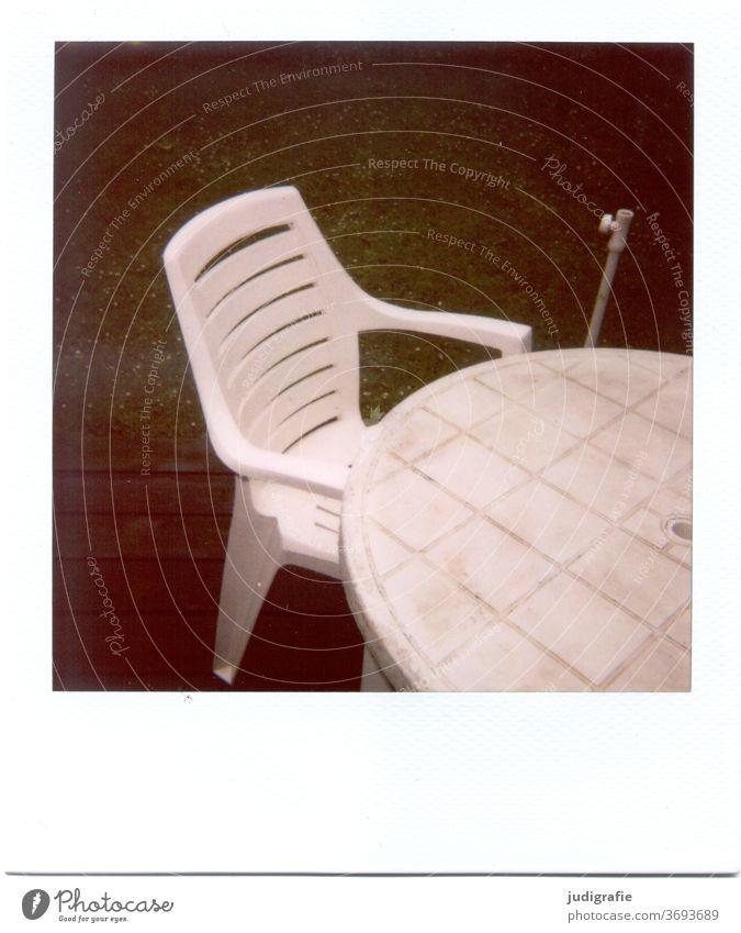 Weißer Gartenstuhl mit Tisch auf Polaroid Möbel Stuhl Plastikstuhl Gartenmöbel Menschenleer Sitzgelegenheit Außenaufnahme Farbfoto Terrasse Sommer Pause alt