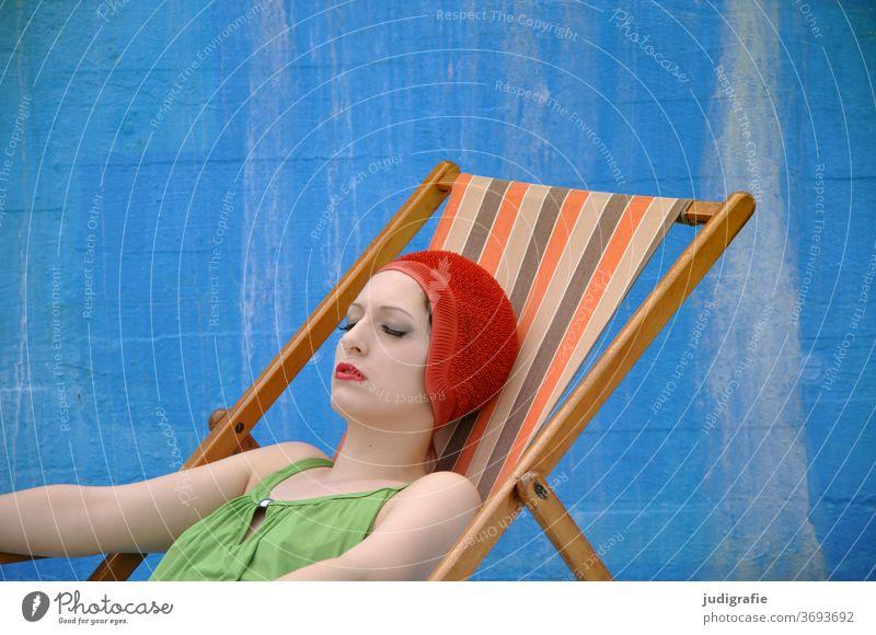 Das Mädchen mit der schönen roten Badekappe und grünem Badeanzug nimmt im Liegestuhl ein Sonnenbad. Eine Sommerliebe. Frau Badebekleidung Badehaube Haut jung