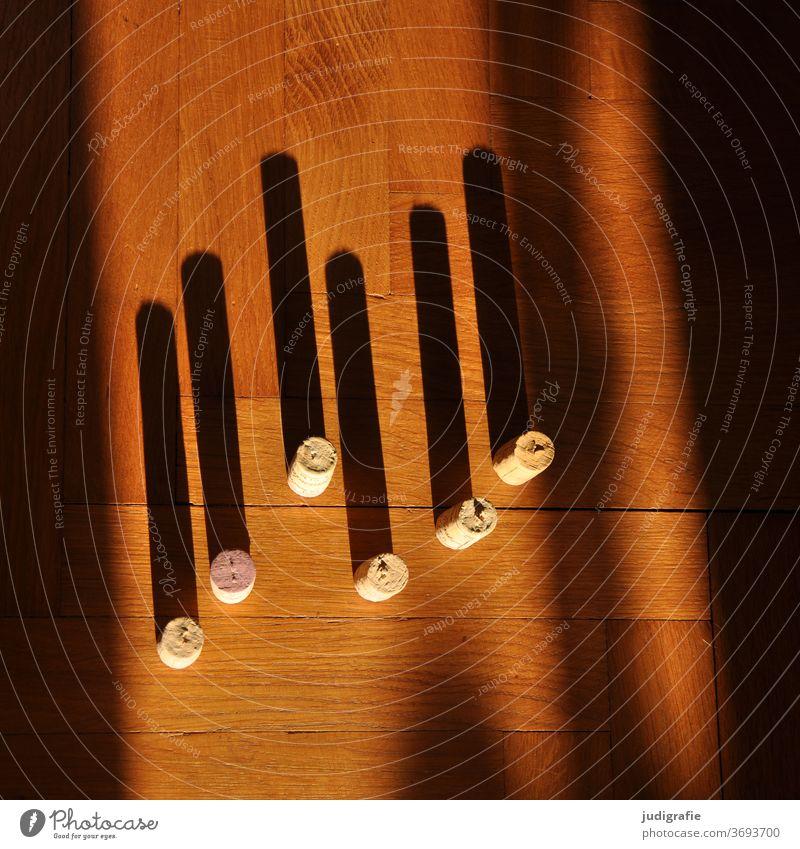 Sechs Korken mit langen Schatten auf Parkett. Licht Parkettboden Warmes Licht warm sechs Striche Linien weinkorken zählen Sonnenlicht abstrakt