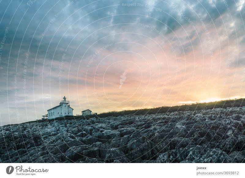 Kleines Haus mit Leuchtturm vor Himmel bei Sonnenuntergang Landschaft Idylle Ruhe Horizont Meer orange felsküste Küste Felsen Sonnenuntrgang Farbfoto