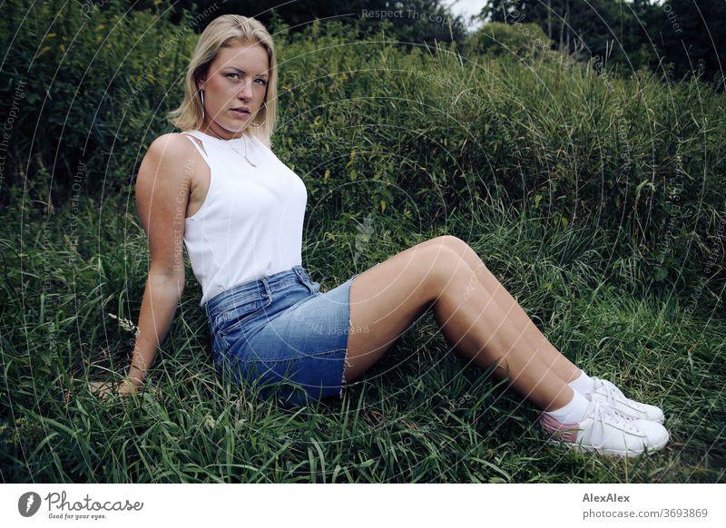 Portrait einer jungen Frau in tiefen Gras junge Frau blond Lächeln Schmuck schön langhaarig Landschaft gebräunt selbstbewußt Sommer natürlich weiblich verliebt
