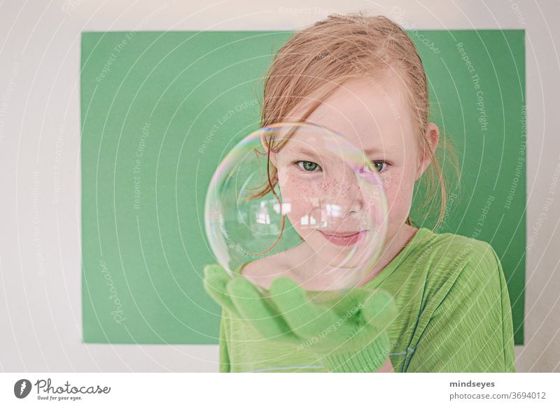 Mädchen in Grün schaut frech durch eine Seifenblase Seifenblasen grün Magie Handschuhe Spielen spass Kindheit Freude lustig Sommersprossen Farbfoto portraitfoto