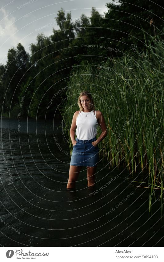 Portrait einer jungen Frau in einem See vor Schilf junge Frau blond Lächeln Schmuck schön langhaarig Landschaft gebräunt selbstbewußt Sommer natürlich weiblich