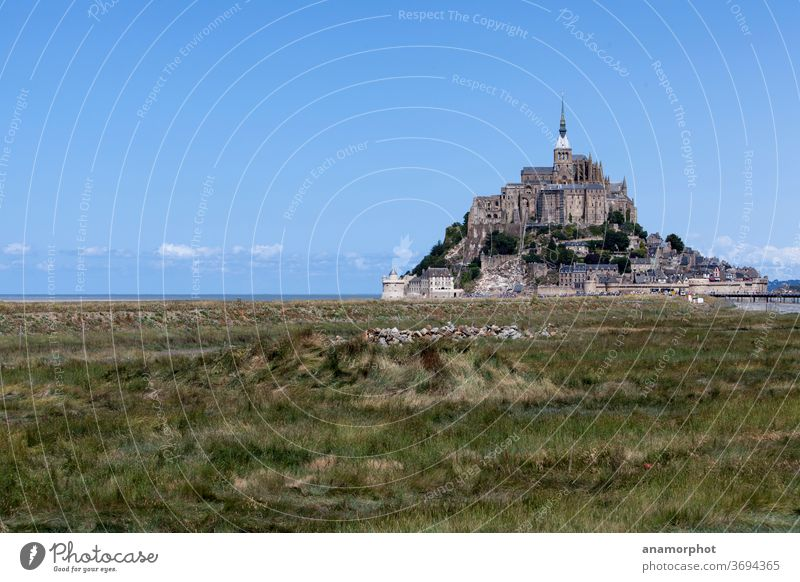 Strohrollen auf einem Feld, im Hintergrund Mont St. Michel Frankreich Bretagne Sommer Sonne Getreideernte blauer Himmel grün schöner Tag Urlaub Reise Ferien