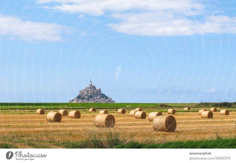 Strohrollen auf einem Feld, im Hintergrund Mont St. Michel Frankreich Bretagne Sommer Sonne Strohballen Getreideernte blauer Himmel gelb grün Wolkenhimmel