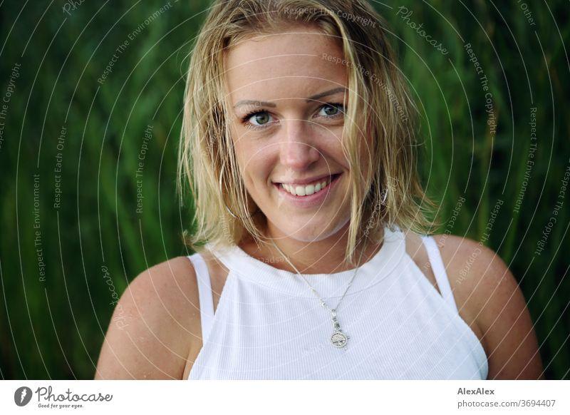 Portrait einer lächelnden, jungen Frau in der Natur junge Frau blond Lächeln Schmuck schön langhaarig Landschaft gebräunt selbstbewußt Sommer natürlich weiblich