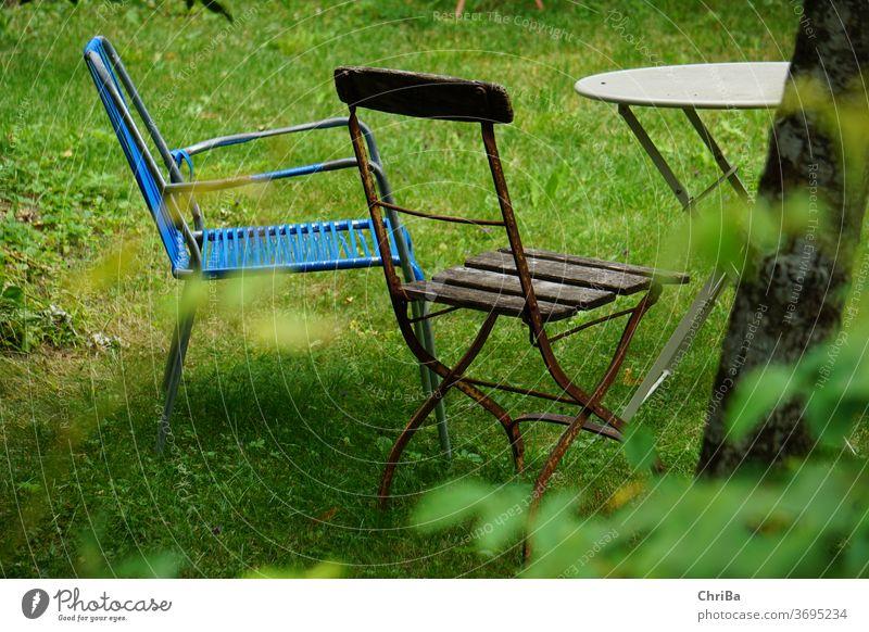 Sitzecke im Garten mit alten, zusammengewürfelten Gartenmöbeln Sitzgelegenheit Tisch Stuhl vintage gemütlich hygge wabisabi Kaffeetisch Gartenstuhl Sommer