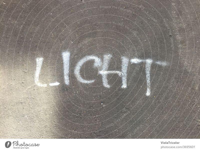 Licht: gesprühter Schriftzug auf Asphalt Straße weiß grau Boden fußboden draußen Tageslicht Lichteinfall Handschrift Typographie Wort Lichtblick Buchstaben