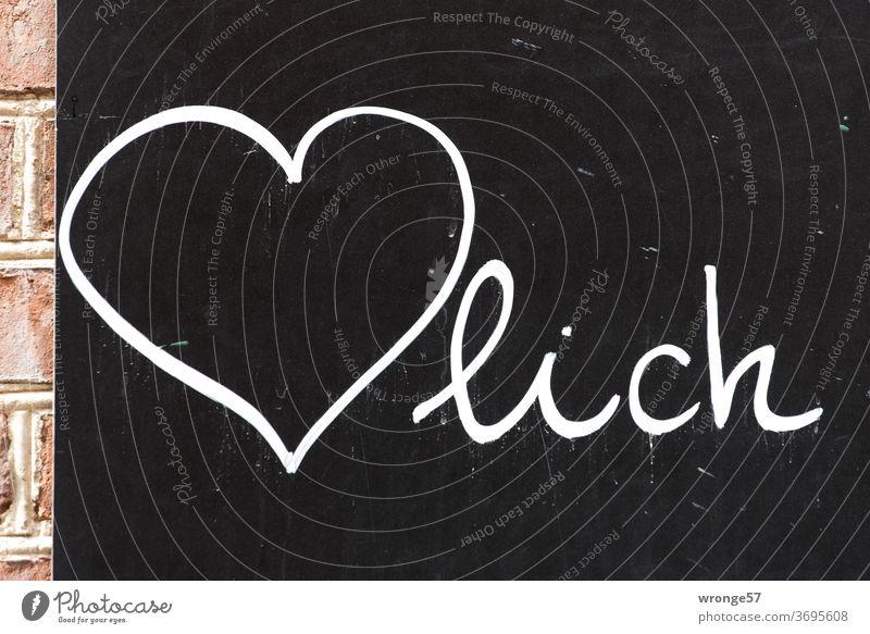 Herzlich mit weißer Kreide auf eine schwarze Tafel gemalt herzlich Aufsteller Farbfoto weiße Kreide schwarzer Untergrund Menschenleer schreiben Schriftzeichen