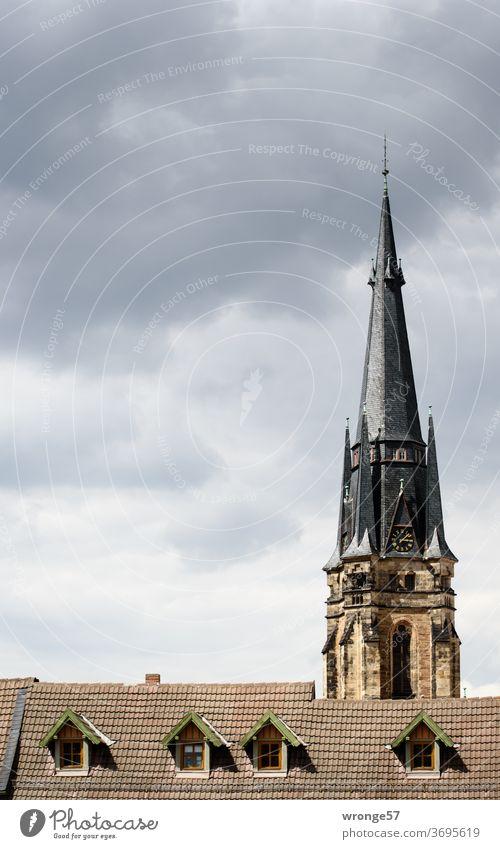 Gegensätze | in der Bauhöhe Gebäudehöhe Kirchturm Wernigerode Hausdach Gauben Kirchturmspitze Himmel Wolkenhimmel bewölkt Kirche Außenaufnahme Farbfoto