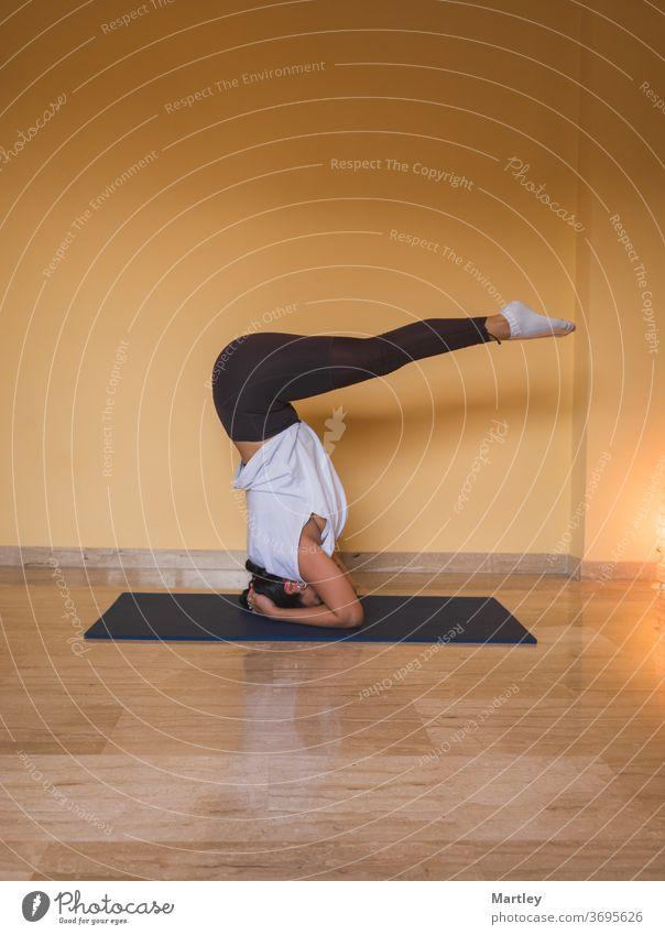 anonyme Frau beginnt unterstützte Kopfstand-Pose. Seitenansicht einer schlanken Frau, die tagsüber zu Hause in einem gemütlichen Wohnzimmer Yoga macht. Mädchen